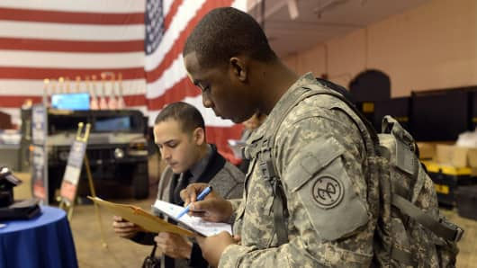 "Soldiers fill out applications during the ""Hiring Our Heroes"", hiring fair for veterans and military spouses."