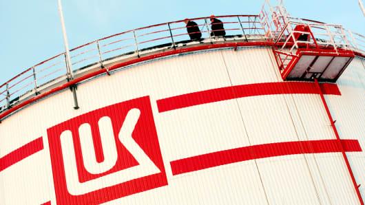 Workers walk along the roof an oil storage tank at Lukoil's Usinskoye oil-field.