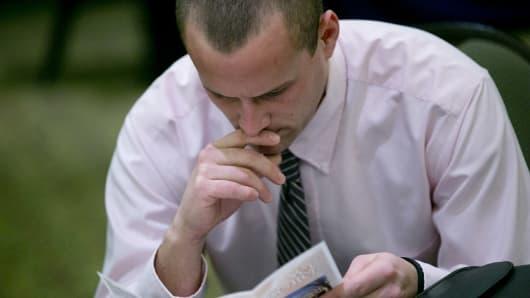 An unemployed worker checks out a brochure at a jobs fair.