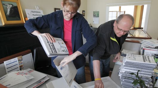 Co-founder of the Medical Maijuana Business Daily Anne Holland and Ron Perry fulfill orders for their Marijuana Business Factbook at the office in Providence.