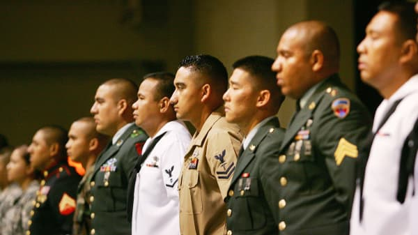 Service members rise after being sworn in as citizens during naturalization ceremonies.