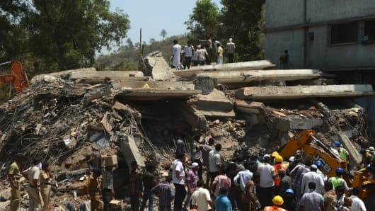 Indian rescue workers and local residents stand near the debris at the site of a building collapse in Thane, on the outskirts of Mumbai last week.