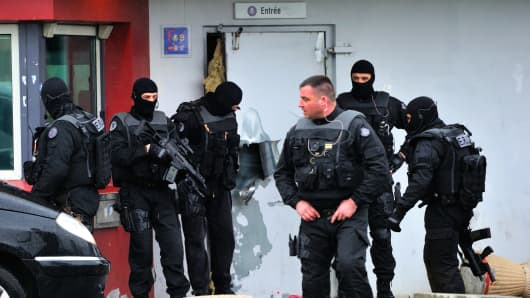 Members of Eris, a regional intervention unit  of the French penitentiary administration are at work in front of a door opened with explosives by an inmate, Redoine Faid, who managed to escape after holding five wardens hostage.