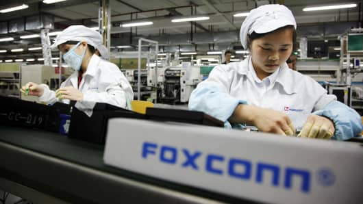 Foxconn employees on the assembly line in Longhua, Shenzhen, China. The company reportedly employed students working overtime at its iPhone factory in Zhengzhou.