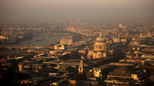 A view over the financial district and St Paul's Cathedral towards the west of the city at sunrise in London.