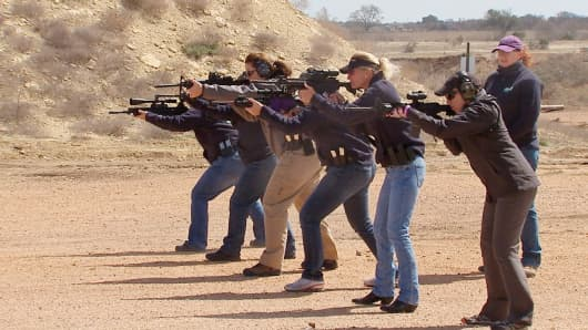 Women at a women's gun club fire AR-15 assault rifles.