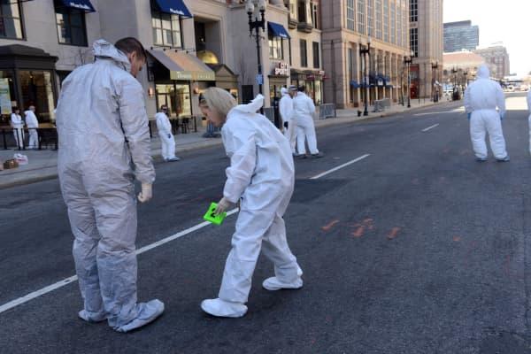 An FBI crime scene investigator places an evidence marker on Boylston Street just past Berkeley Street near the scene of the Boston Marathon bombing April 17, 2013 in Boston, Massachusetts