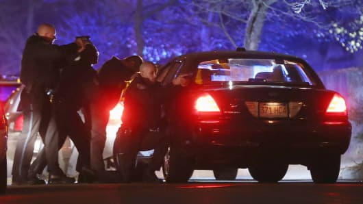 Police with guns drawn search for a suspect on April 19, 2013, in Watertown, Mass.