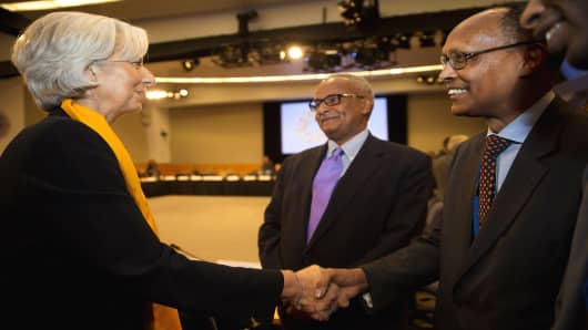 IMF Managing Director Christine Lagarde greets Somalia's Minister of Finance Mohamud Hassan Suleiman as Somalia's Bank Governor Abdusalam Omer looks on.