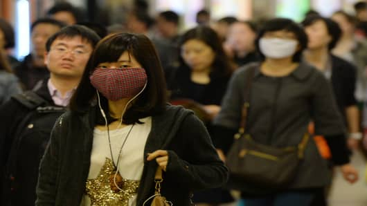 Shanghai commuters wear face masks as the latest H7N9 bird flu virus continues to claim victims.