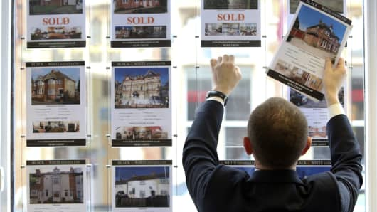 A real estate agent places an ad for a house in the window display board.