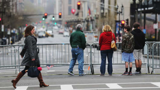 People stand at a barricade blocking a still closed section of Boylston Street near the site of the Boston Marathon bombings.