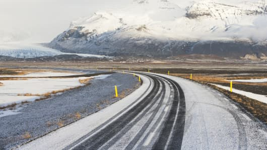 Snowy road curving past the mountains, Iceland.