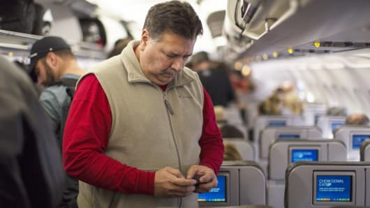 A passenger on Jet Blue Airways checks his cell phone before he disembarks at the Long Beach, California airport.