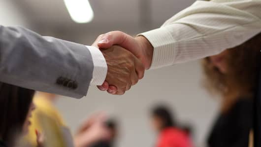A job seeker (R) shakes hands with a recruiter.