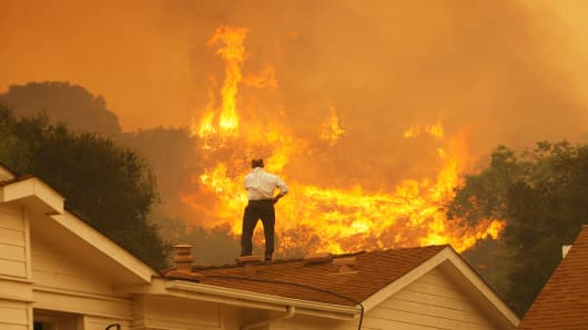 A man on a rooftop looks at approaching flames as the Springs fire continues to grow on May 3, 2013 near Camarillo, California.