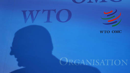 A silhouette of an official is seen with a logo of the World Trade Organization (WTO) as background at the Trade organisation headquarters in Geneva.