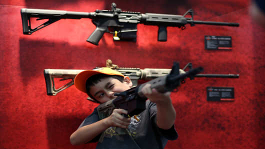 A young attendee inspects an assault rifle during the 2013 NRA Annual Meeting and Exhibits at the George R. Brown Convention Center on May 4, 2013 in Houston, Texas.