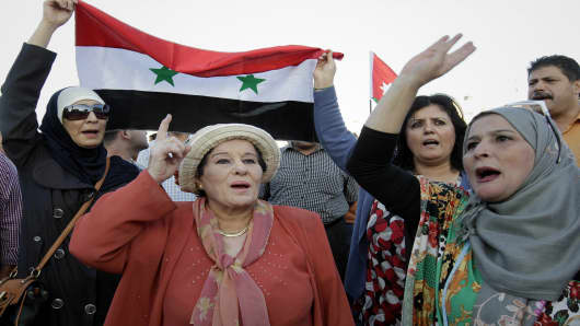Jordanian opposition party members carry the Syrian flag and shout slogans against Israel during a protest condemning the air strike in Syria, near the Israeli embassy in Amman on May 5, 2013.