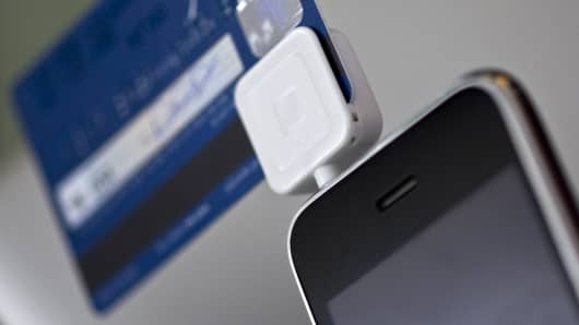 Square, a credit card reader, is arranged on an Apple iPhone.