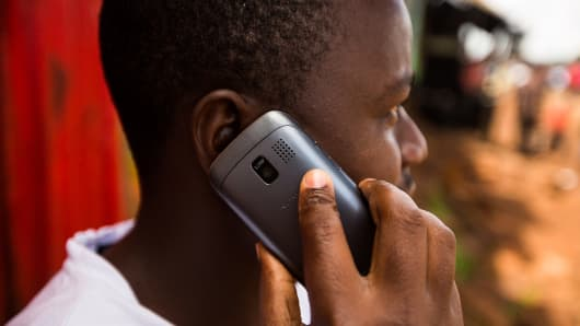 A resident speaks on a Nokia Asha mobile phone on a street in Nairobi, Kenya.