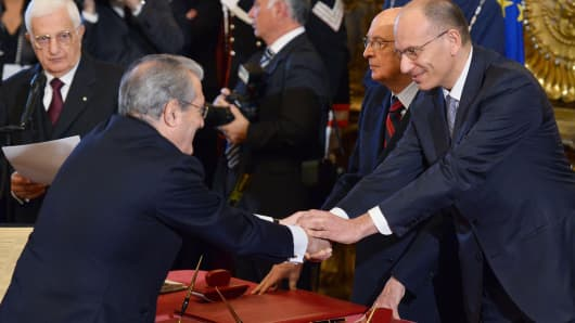 New Italian Minister of Economy and Finance Fabrizio Saccomanni (L) shakes hands with Prime Minister Enrico Letta during the swearing in ceremony of the new government on April 28, 2013.