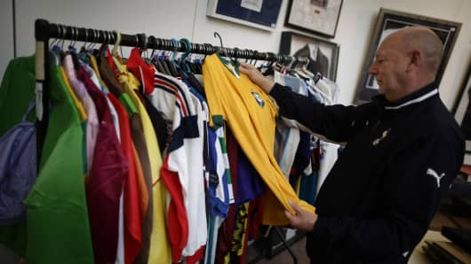 A buyer looks at a Brazilian international soccer jersey at Sotheby's in London