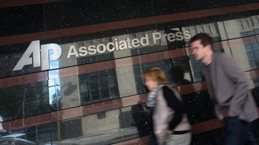 A couple walk past the offices of the Associated Press in Manhattan, New York May 13, 2013.