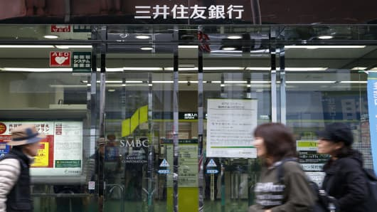 Pedestrians walk past a Sumitomo Mitsui Banking Corp. branch in Tokyo, Japan