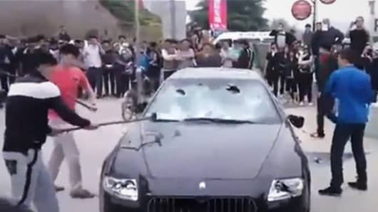 A wealthy Chinese businessman hired a crew to smash his Maserati Quattroporte at the Qingdao Auto Show. Here, the crew takes sledgehammers to the windshield of the supercar.