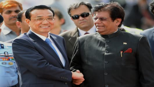 Chinese Premier, Li Keqiang (L) is welcomed by Indian Minister of State for External Affairs, E. Ahmed on his arrival at Palam Airport in New Delhi on May 19, 2013