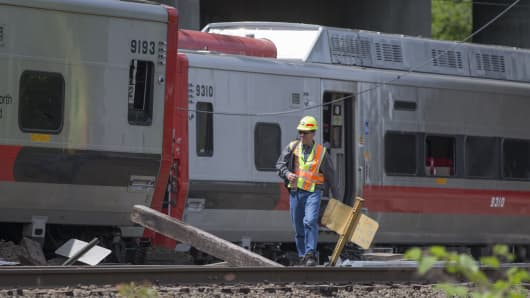 A Connecticut state investigator examines the scene of a Metro North train collision on May 18, 2013