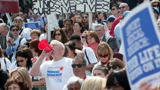 People cheer at a rally for medical research where more than 170 partnering organizations 'called on our nation's policymakers to make lifesaving medical research funding a national priority.'