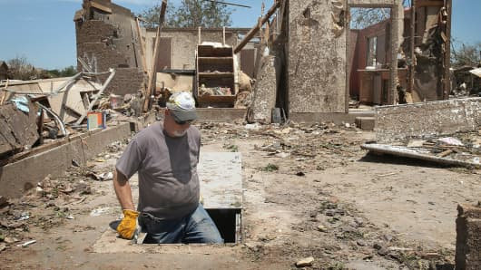 Dean Dye looks over a storm shelter in a home that was destroyed by a tornado on May 22, 2013 in Moore, Oklahoma.
