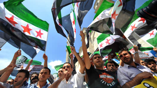 Protestors wave Free Syria's flags and chant slogans during a demonstration.