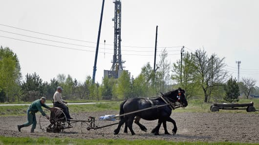Farmers sow a field in front of a drilling rig exploring for shale gas in the eastern Polish village of Grzebowilk.