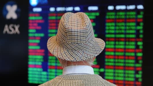 A retiree watches stock prices on the Australian Stock Exchange (ASX) in Sydney, Australia.
