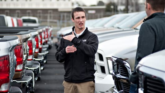 Salesman Steve Ferman, center, discusses the features Dodge Ram pickup truck with Joe DeLucia at Sam Leman Chrysler, Dodge, Jeep in Peoria, Illinois, U.S