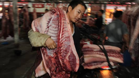 A Chinese vendor carries a slaughtered pig to his motorcycle at an abattoir, as he heads back to his stall at a market in Hefei, east China's Anhui province.