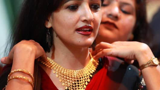 Customer tries on a gold necklace in New Delhi.