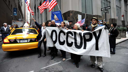 Demonstrators with 'Occupy Wall Street' march in the streets near the New York Stock Exchange.