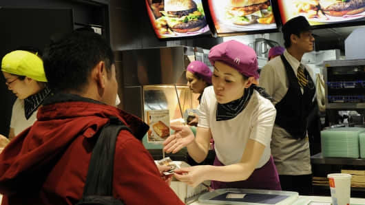 Customers buy fast food at a McDonalds restaurant in Tokyo.
