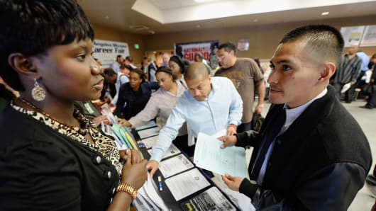 Job seekers pick up fliers adverising jobs during Los Angeles Mission's 12th annual Skid Row Career Fair on June 6, 2013 in Los Angeles, California