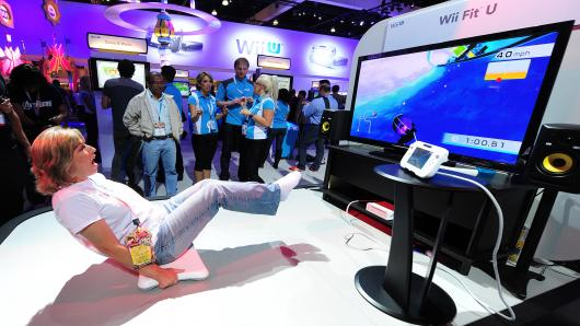 A woman works her abs while playing the 'Core Luge' game from Wii Fit U from the new Wii U console on the third day of the E3 videogame extravaganza in Los Angeles on June7, 2012 in California.
