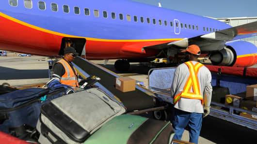 Southwest Airlines employee prepares to load bags onto a plane at Love Field Airport in Dallas, Texas.