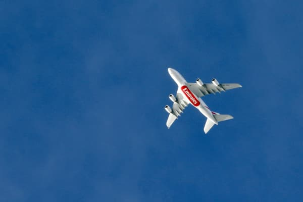 An Emirates A380 airbus plane flying over Paris