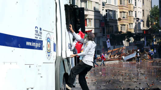 A protester attacks a police vehicle in Taksim Square, Istanbul, Turkey.