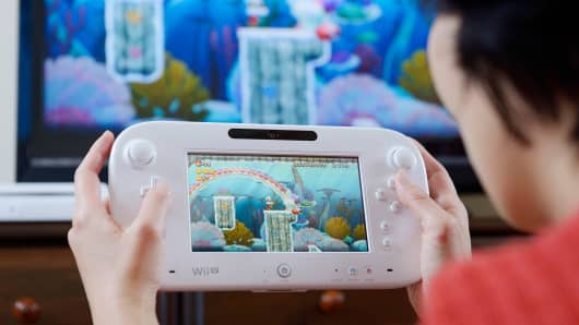 "A Nintendo Wii U touch-screen controller displaying the ""Super Mario Bros."" game"