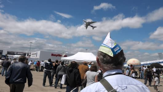 A visitor watches the Airbus A380 during its flying display at the last Paris Air Show in 2011