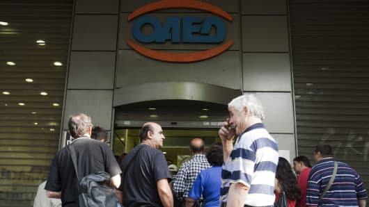 Jobseekers wait outside the entrance to an OAED employment office in Athens, Greece.